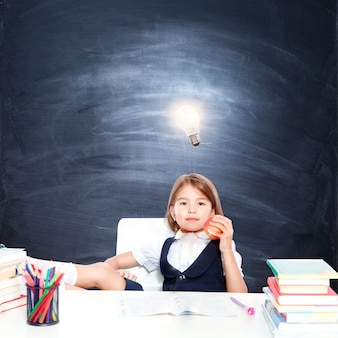 頭上に電球と黒板で若いかわいい女の子
