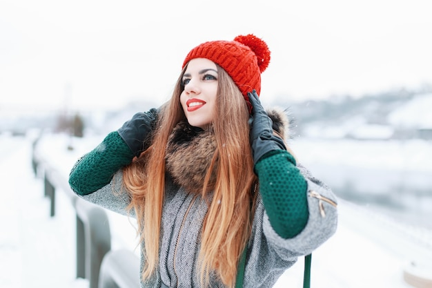 Young cute girl in the cold winter weather near the river