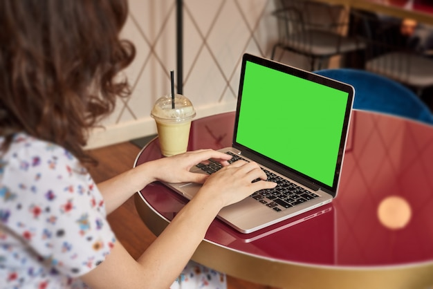 Young cute girl in dress working on a laptop in coffee shop