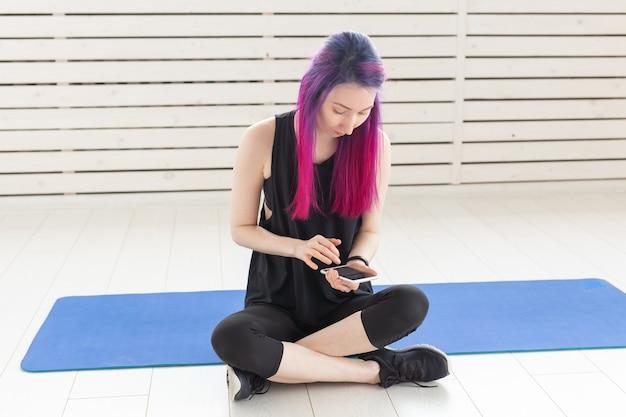 Молодая милая девушка фитнес-модель с яркими волосами подсчитывает калории, сожженные после тренировки. понятие о спорте и фитнесе.