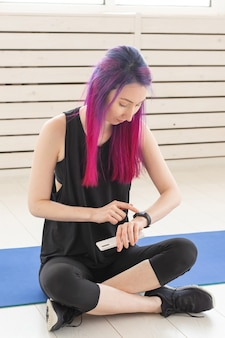 Young cute girl fitness model with bright colored hair is counting calories burned after a workout. concept of sport and fitness. advertising space