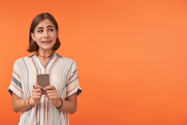 젊은 귀여운 소녀 스마트 폰을 들고 오른쪽 오렌지 벽에 복사 공간에서보고, 어색한 찾고. 줄무늬 셔츠, 중괄호, 목걸이 및 팔찌 착용