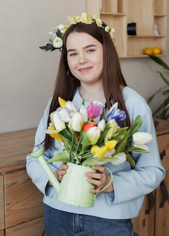 Young cute girl holding watering can with flowers