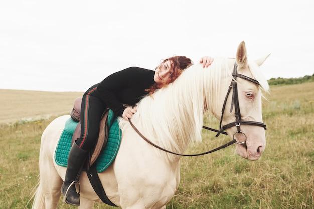 若いかわいい女の子がまたがって座っている間彼女の馬を抱き締めます。彼女は動物が好き