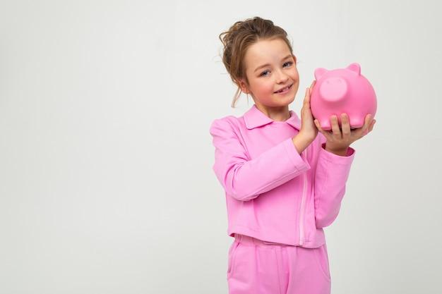 ピンクのスーツのかわいい少女が空白の白い壁に貯金箱を保持します