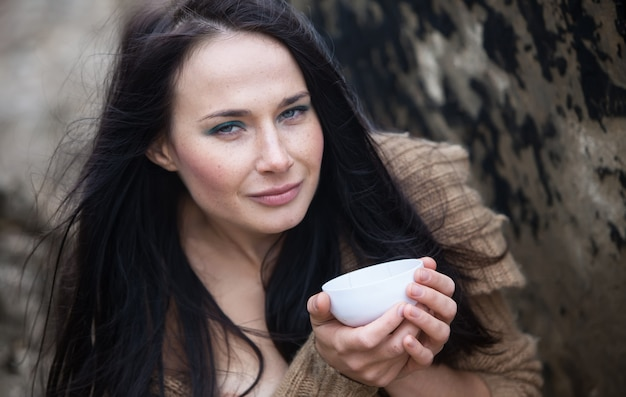 Young cute girl in a knitted sweater against an old concrete wall drinking tea from a white cup