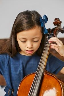 첼로 연주하는 방법을 배우는 귀여운 소녀