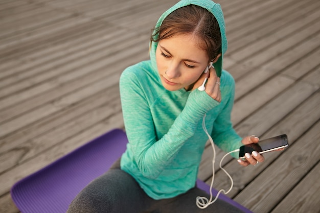 Young cute girl , listening new playlist on headphones after morning yoga and enjoy the sun.