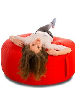 白で隔離の丸い形の赤いお手玉の椅子に横たわって若いかわいい女の子
