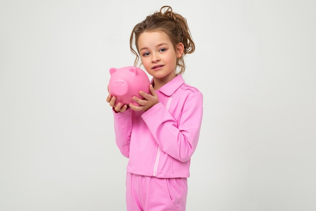 Young cute girl in a pink suit holds a piggy bank on a white wall with blank space