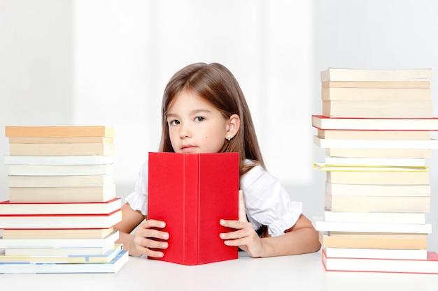 테이블에 앉아서 책을 읽는 어린 귀여운 소녀