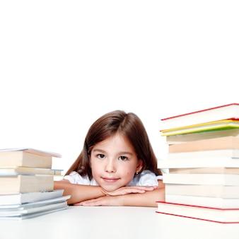Молодая милая девушка сидит за столом и читает книгу
