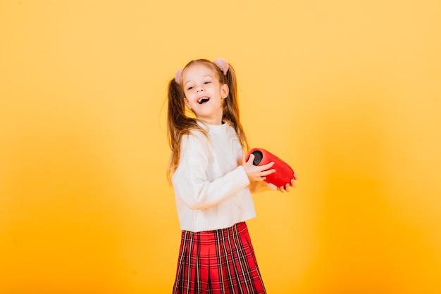 웃 고 노란색 스튜디오 배경에 무선 휴대용 스피커와 춤 젊은 귀여운 소녀. 새해 분위기.