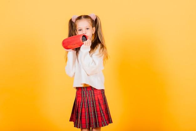 笑顔とワイヤレスポータブルスピーカーで踊る若いかわいい女の子