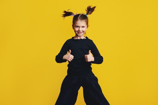 Молодая милая девушка улыбается и показывает палец вверх обеими руками во время прыжка