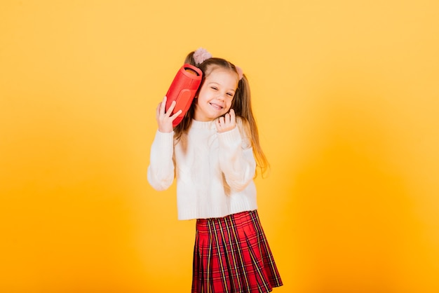 Young cute girl smiling and dancing with wireless portable speaker on yellow studio background. new year mood.