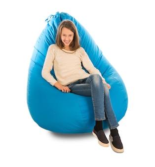 白で隔離の青いお手玉に座って笑っている若いかわいい女の子