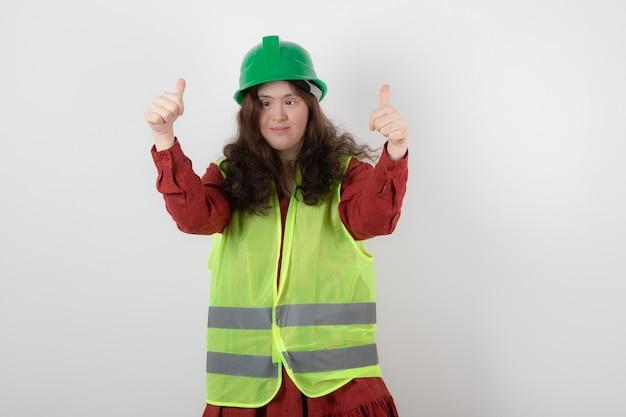 Giovane ragazza carina in piedi nel casco verde e mostrando le mani in alto.