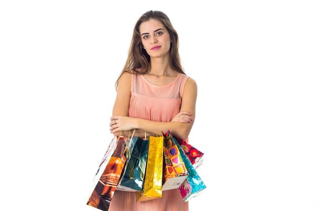 귀여운 소녀가 똑바로 서서 쇼핑백을 닫고 있습니다