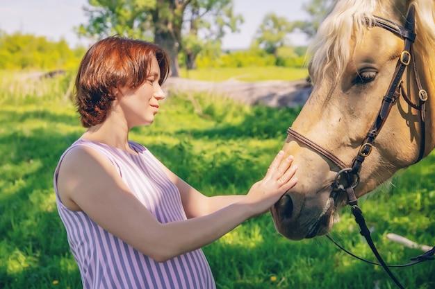Молодая милая девушка гладит лошадь на открытом воздухе