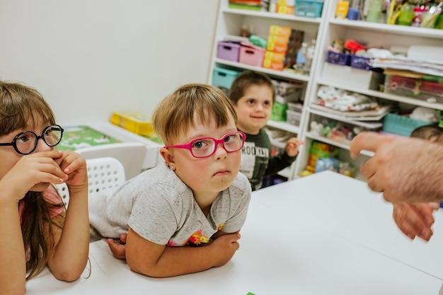 회색 셔츠와 다른 아이들과 함께 흰색 책상에 앉아 공부하는 분홍색 안경에 다운 증후군이있는 젊은 귀여운 소녀.