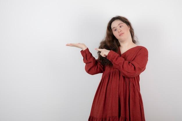 다운 증후군이 있는 귀여운 소녀가 서서 손을 가리키고 있습니다.
