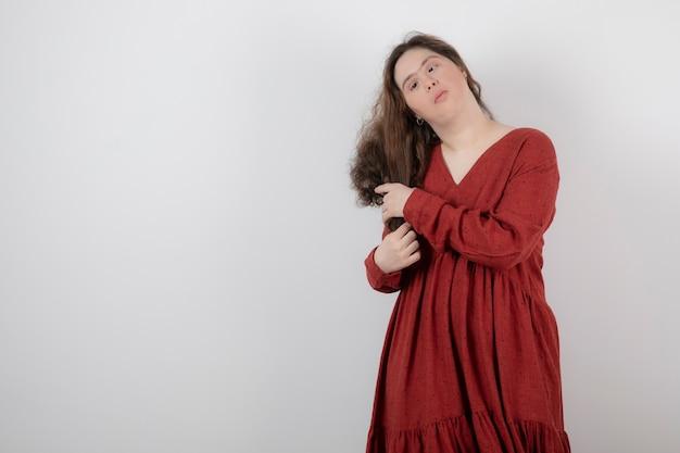 다운 증후군이 있는 귀여운 소녀가 서서 포즈를 취하고 있습니다.