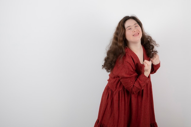Young cute girl with down syndrome standing and posing .