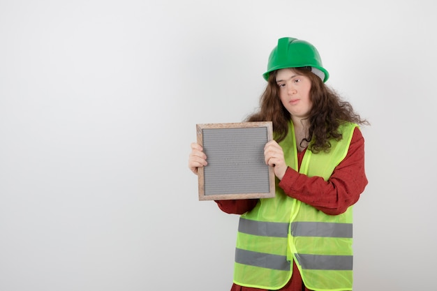 Young cute girl with down syndrome standing in vest and holding a frame .