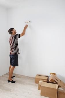 Молодой симпатичный парень с бородой в полосатой футболке и синих шортах красит белую стену в квартире по ипотеке в новостройке.