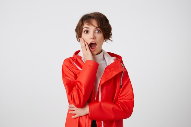 Giovane ragazza dai capelli corti stupita felice carina in golf bianco e cappotto impermeabile rosso, guardando con la bocca spalancata, tocca la guancia, sente notizie incredibili. in piedi.