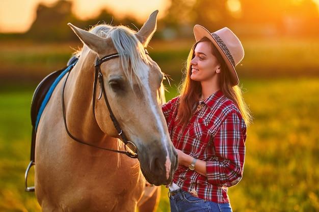 Молодая милая счастливая радостная довольная улыбающаяся пастушка с красивой белокурой лошадью паломино на лугу на закате
