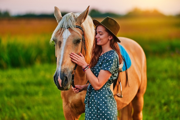 Молодая милая счастливая радостная довольная улыбающаяся женщина обнимает и гладит красивую белокурую лошадь паломино на лугу на закате