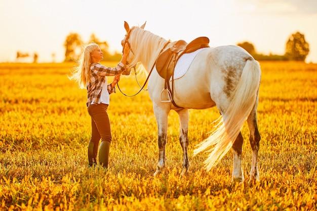 Молодая милая счастливая радостная довольная улыбающаяся женщина обнимает и гладит красивую белую лошадь на лугу на закате в золотой час