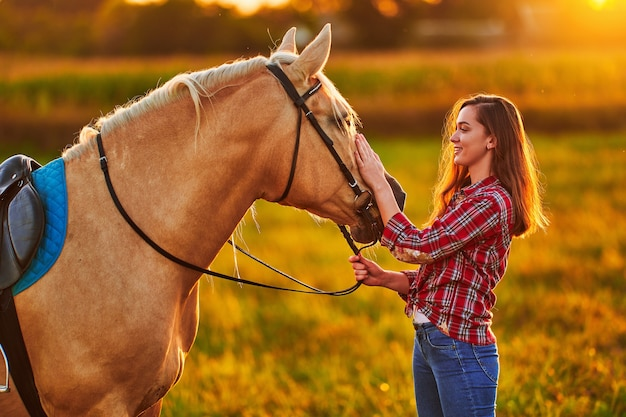 Молодая милая счастливая радостная довольная улыбающаяся женщина гладит красивую белокурую лошадь паломино на лугу на закате