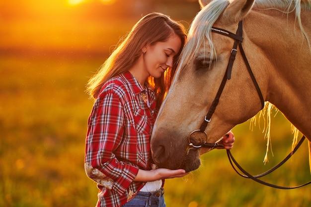 Молодая милая счастливая радостная довольная улыбающаяся женщина с закрытыми глазами, наслаждающаяся объятиями и поглаживанием красивой белокурой лошади паломино на лугу на закате
