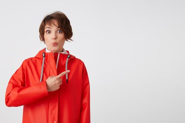 빨간 비옷에 젊은 귀여운 행복 짧은 머리 여자, 멋진 소식을 듣습니다. 주의를 끌고 복사 공간을 손가락으로 가리 킵니다. 서 있는.