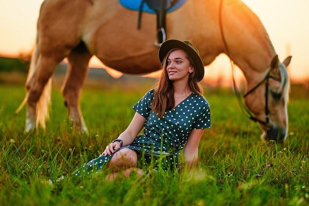 Молодая милая счастливая стильная радостная модная романтическая довольная улыбающаяся женщина в шляпе и платье в горошек с красивой белокурой лошадью паломино на лугу на закате