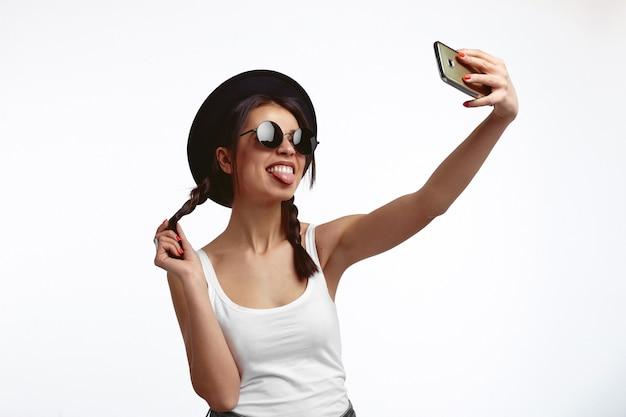 젊은 귀여운 hipster 젊은 여자 selfie를 복용 하 고 흰 벽에 혀를 보여