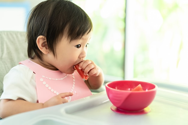 Young cute kid on baby high chair feeding seat holding watermelon with smile face at home, enjoy self eating meal with happiness.