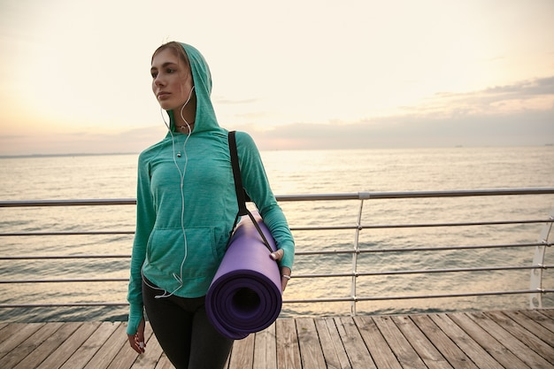 海辺を歩いて、ヨガの練習に行き、朝のストレッチをし、紫色のヨガマットを持って目をそらしている若いかわいい女性。