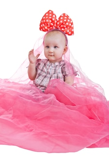 Young cute and lovely little girl (or little kid) wearing pink dress with pink and white polka dot bow is sitting down isolated on a white background