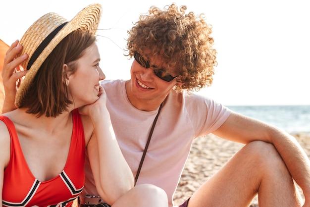 屋外のビーチに座っている若いかわいい愛情のあるカップルの友人