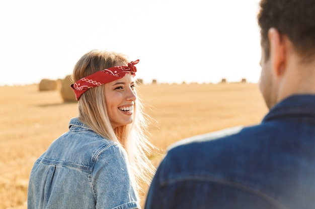 野外を歩いてフィールドに立っている若いかわいい愛情のあるカップル。