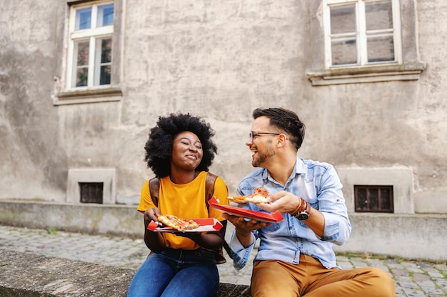 Young cute multicultural hipster couple sitting outdoors and eating pizza.