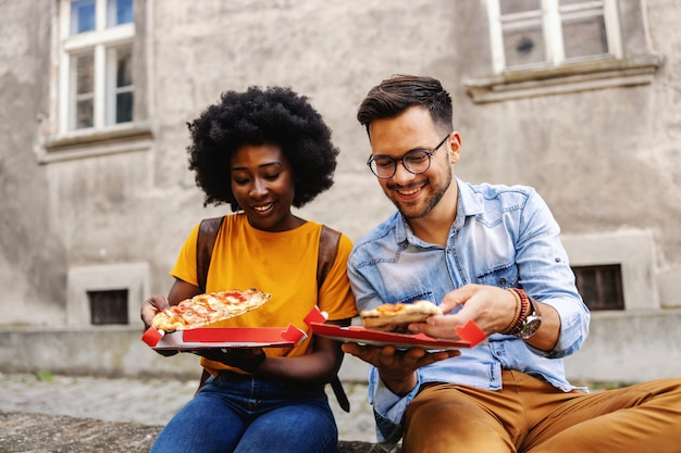 Young cute multicultural hipster couple sitting outdoors and holding pizza.