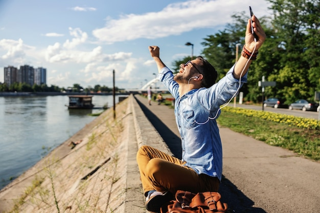川のそばに座って、美しい晴れた日に音楽を楽しんでいる若いかわいい大喜びのヒップスター。