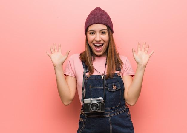 Молодая милая женщина фотографа празднуя победу или успех