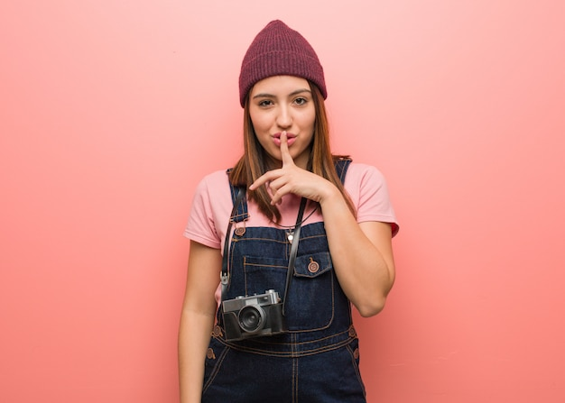 Young cute photographer woman keeping a secret or asking for silence