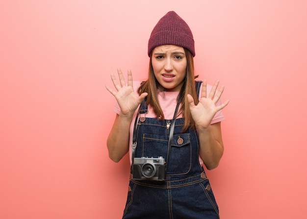 Young cute photographer woman rejecting something doing a gesture of disgust